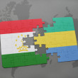 Постер, плакат: Puzzle with the national flag of tajikistan and gabon on a world map