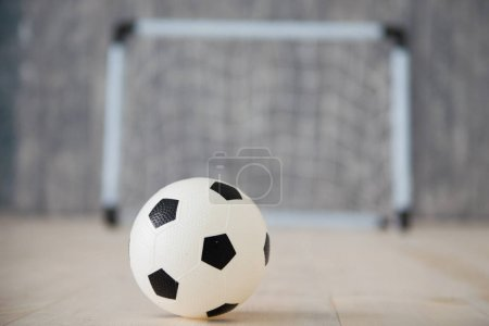 A soccer ball in a small gate on a gray background. Mini football.