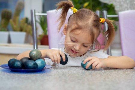 Photo pour Petite charmante fille européenne avec deux queues de cheval assise à une table et jouant avec des œufs de Pâques peints. - image libre de droit