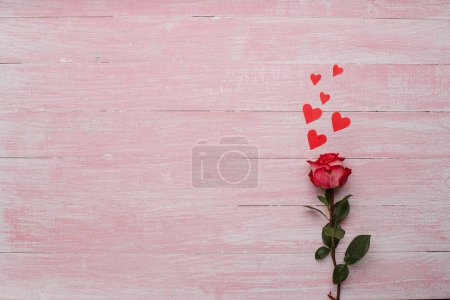 Photo pour Heureuse Saint Valentin amour célébration dans un style rustique et isolé. Petits coeurs rouge et une fleur rosa sur fond en bois. - image libre de droit