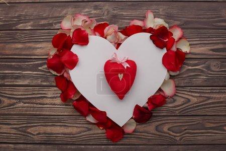 Photo pour Heureuse Saint Valentin amour célébration dans un style rustique et isolé. Coeur de pétales de roses sur fond en bois. - image libre de droit
