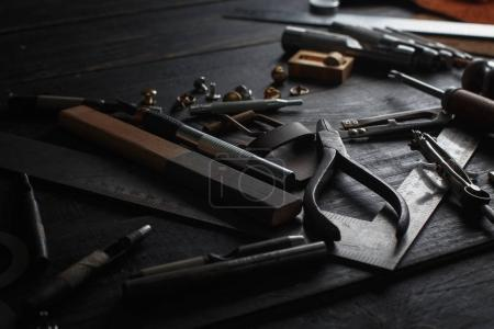 Photo for Set of leather craft tools on wooden background. Workplace for shoemaker. Piece of hide and working handmade tools on a work table - Royalty Free Image