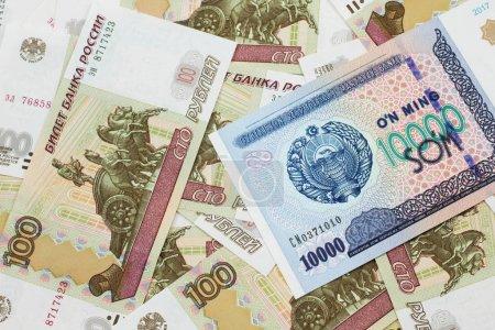 Photo pour Une image rapprochée d'un billet de dix mille som ouzbèke sur un fond de la Fédération de Russie cent billets de rouble en macro - image libre de droit