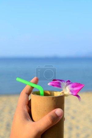 Photo pour Boisson de bienvenue avec verre de bambou et décorer avec une orchidée violette sur sable, fond mer et ciel bleu. - image libre de droit