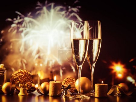 Photo for Two champagne glasses against holiday lights and fireworks - new year celebration - Royalty Free Image