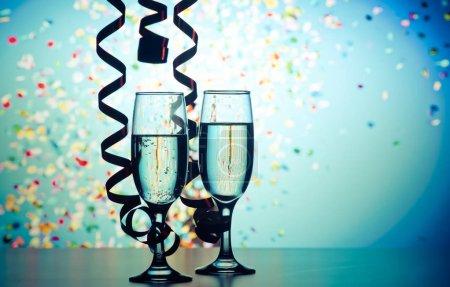 Photo pour Deux verres de champagne avec des rubans et de confettis tombant - célébrations du nouvel an - image libre de droit