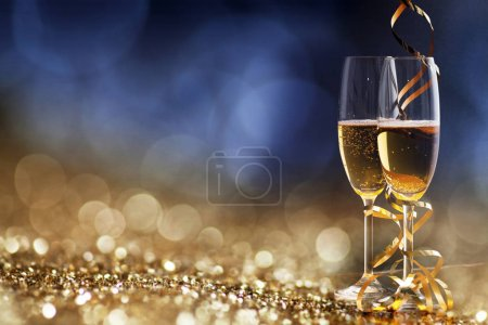 Photo for Two champagne glasses with ribbons against holiday lights and fireworks - New Year celebrations - Royalty Free Image