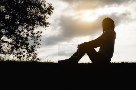 Photo for Sad and depressed woman sitting alone at the field during beautiful sunset with park background. Selective focus - Royalty Free Image