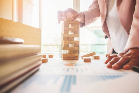 Photo for Hand of business woman planning  risk and strategy in business.Businessman gambling placing wooden block on a tower. - Royalty Free Image
