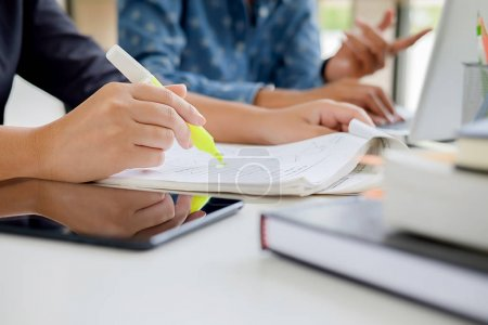 Photo for Education concept. Students studying and brainstorming campus concept. Close up of students discussing their subject on books textbooks and writing to notebook. Selective focus. - Royalty Free Image