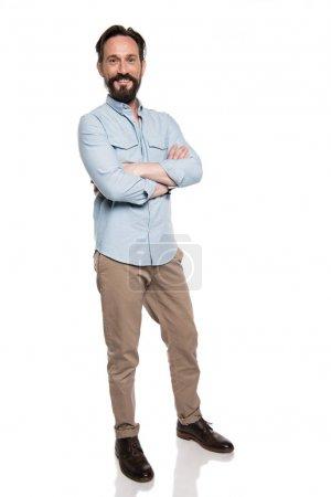 Photo pour Adulte souriant homme en vêtements décontractés debout avec les bras croisés et regardant la caméra isolée sur blanc - image libre de droit