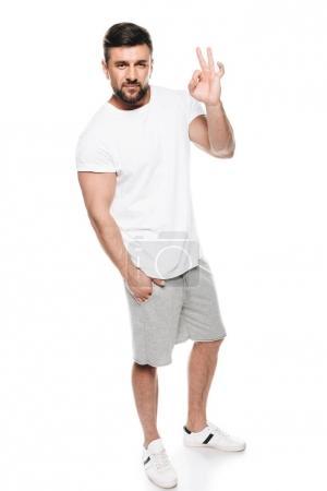 Photo pour Portrait d'un bel homme en t-shirt blanc gestuel ok signe isolé sur blanc - image libre de droit