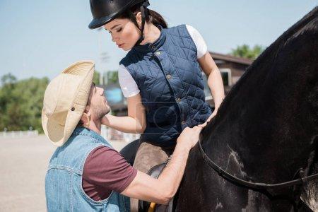 Photo pour Jolie femme en casque de jockey assis à cheval et à la recherche sur le jeune homme au chapeau de cowboy - image libre de droit