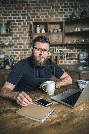 Photo pour Freelancer confiant assis à table avec ordinateur portable et le smartphone tout en regardant la caméra - image libre de droit