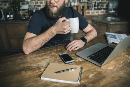 Photo for Cropped view of bearded freelancer drinking coffee and working with laptop in home office - Royalty Free Image