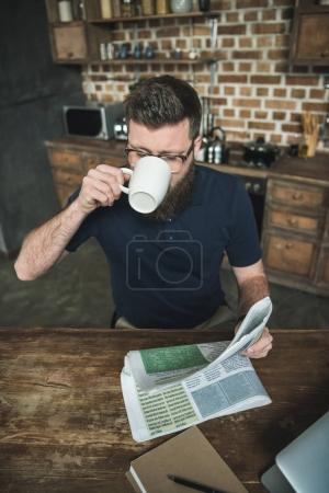 Photo for High angle view of man drinking coffee while reading newspaper at home - Royalty Free Image