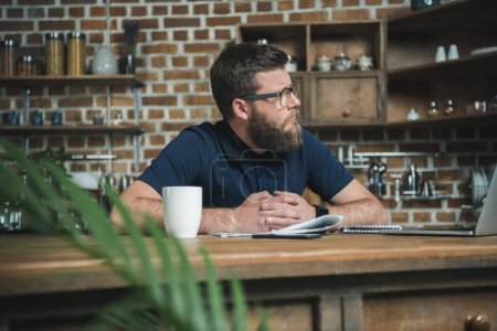 Photo for Portrait of pensive bearded man in eyeglasses sitting at workplace in home office - Royalty Free Image