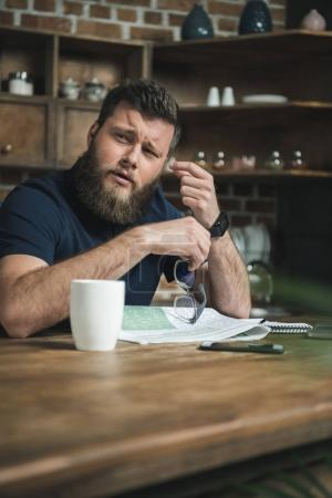 Tired man with newspaper on table