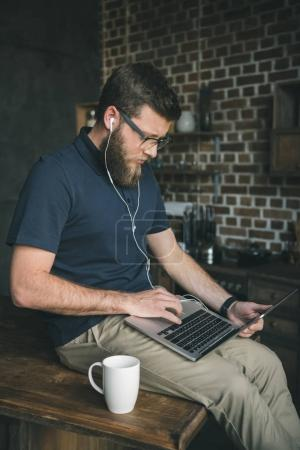 Photo for Young casual man in glasses using laptop and listening music at home - Royalty Free Image