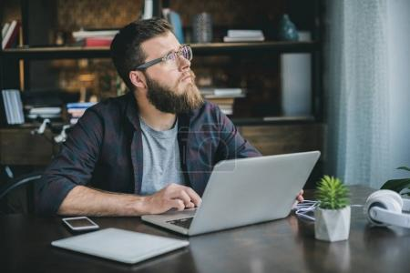 Photo for Pensive bearded man typing on laptop while sitting at home - Royalty Free Image