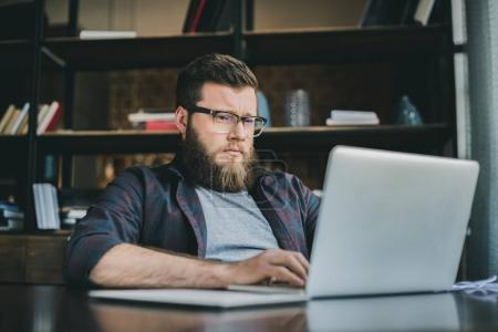 bearded man working on laptop at home