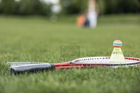 Photo pour Vue rapprochée de deux raquettes de badminton et volant sur l'herbe verte - image libre de droit