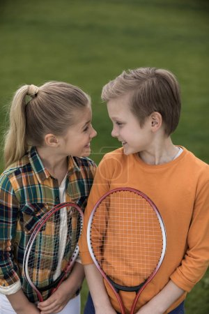 Photo for Cute happy siblings holding badminton racquets and smiling each other - Royalty Free Image