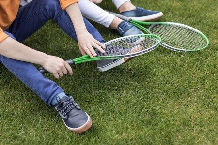 kids holding badminton rackets