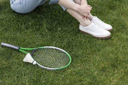 Photo pour Recadrée tir de femme assise sur le sol avec un équipement de badminton près de - image libre de droit