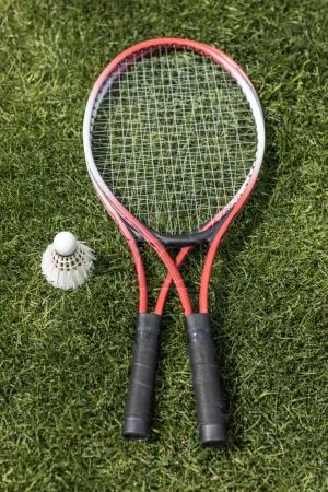 badminton rackets with shuttlecock on grass field