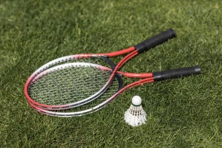 badminton rackets with shuttlecock on grass