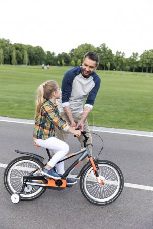 father teaching daughter riding on bicycle