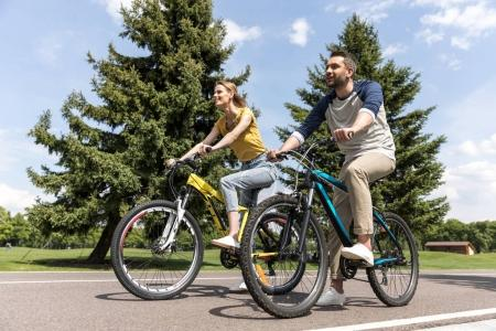 Photo for Young casual couple riding on bicycles in park at daytime - Royalty Free Image