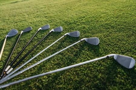 Photo pour Vue rapprochée de l'ensemble des clubs de golf brillants disposés sur l'herbe - image libre de droit