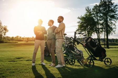Photo for Three smiling men standing with crossed arms near golf clubs in bags - Royalty Free Image