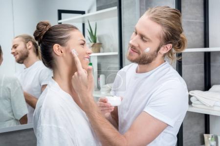 Photo pour Jeunes barbus mari appliquant la crème pour le visage sur la joue de son épouse dans la salle de bain - image libre de droit