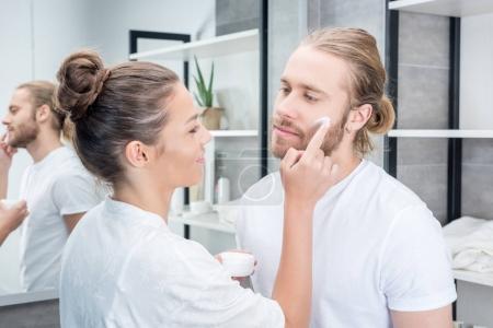 Woman applying cream at husband