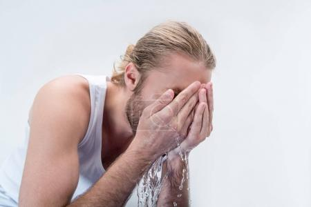 Young man washing face