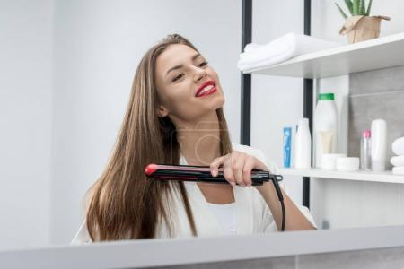 Photo for Smiling beautiful young woman in bathrobe straightening hair at home - Royalty Free Image