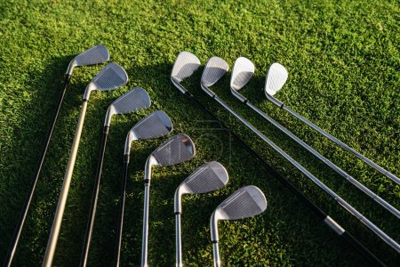 Photo pour Clubs de golf brillants disposés sur le terrain herbeux vert - image libre de droit