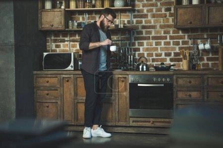 Photo pour Vue latérale de l'homme faisant la tasse de café dans la cuisine à la maison - image libre de droit