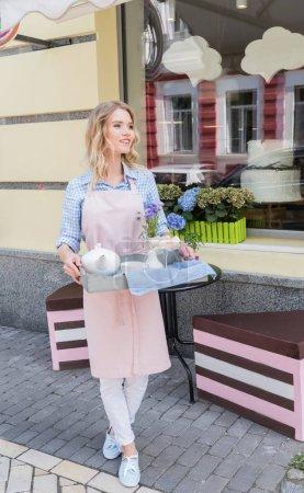 Waitress holding tea set