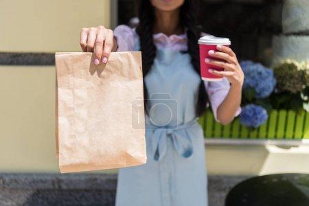 Waitress holding paper bag