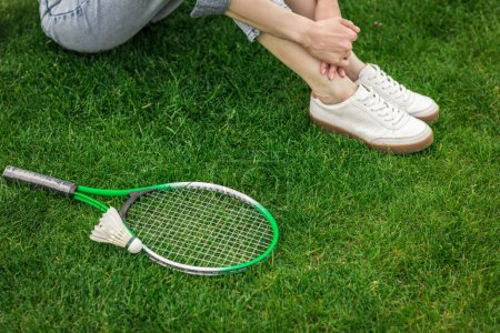 Photo for Cropped shot of woman sitting on ground with badminton equipment near by - Royalty Free Image