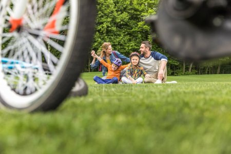 Photo for Happy casual family spending time in park at daytime, bicycle on foreground - Royalty Free Image