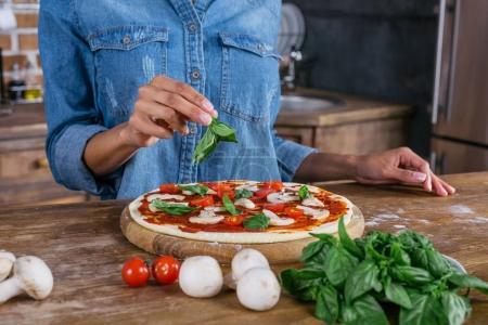 Photo pour Plan recadré de la femme mettant des feuilles de basilic sur la pizza crue - image libre de droit