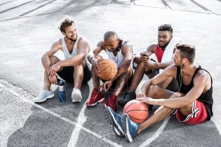Photo for Multiethnic group of basketball players resting on court together - Royalty Free Image