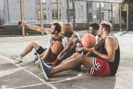 Photo for Multiethnic group of men taking selfie on smartphone while sitting on court after basketball game - Royalty Free Image