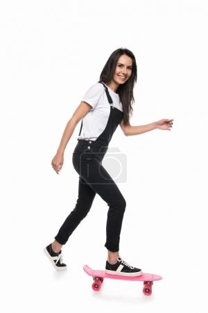 Photo for Happy beautiful young woman skateboarding and smiling at camera isolated on white - Royalty Free Image