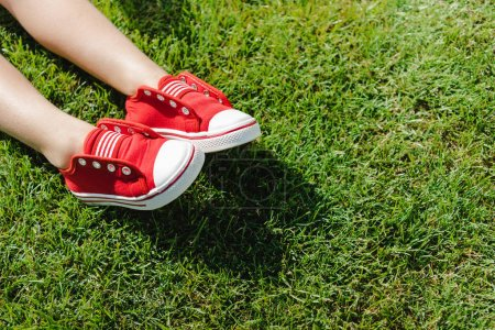 Child in sneakers on grass